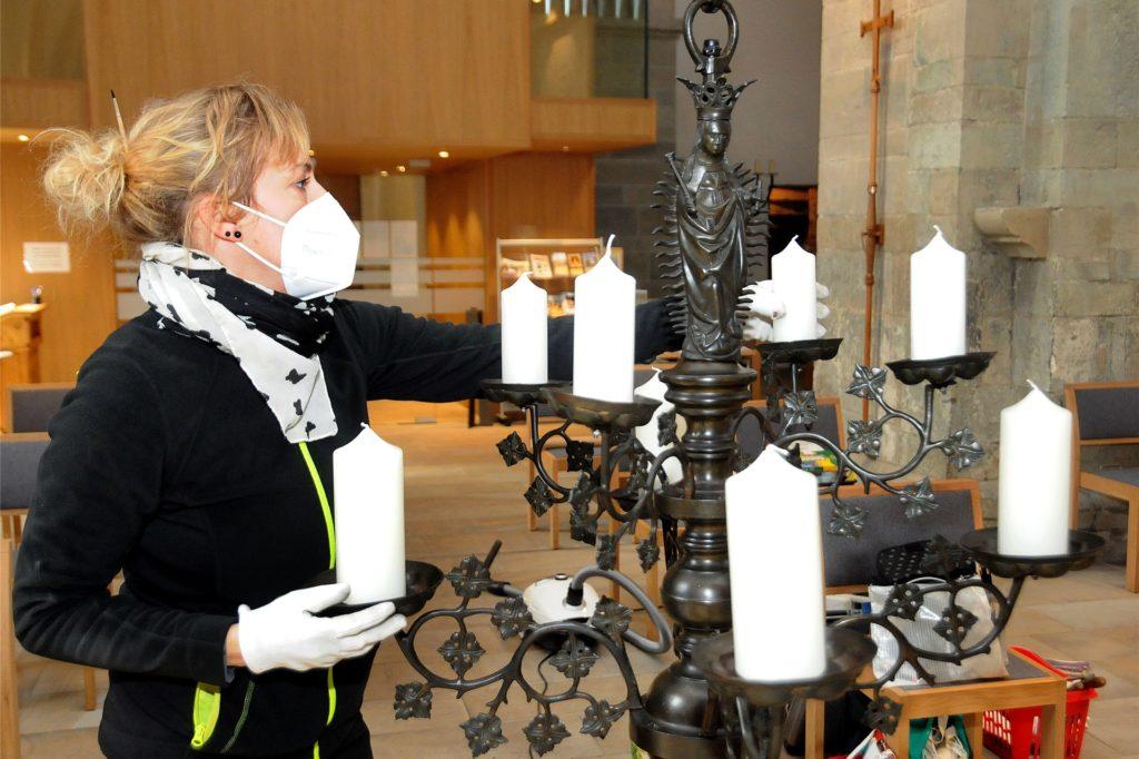 Mit höchster Konzentration stellt Restauratorin Dorothee Brück die Kerzen in den Marienleuchter. Sie müssen exakt senkrecht ausgerichtet sein, bevor das Kunstwerk hoch zur Decke gezogen wird.