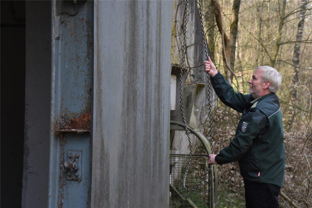 Revierförster Horst Böke zieht an einer Kette, um die schwere Stahltür des Bunkers zu öffnen.