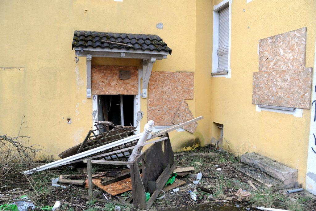 Die verbretterte Tür ist bereits aufgebrochen worden, davor liegt jede Menge Gerümpel.