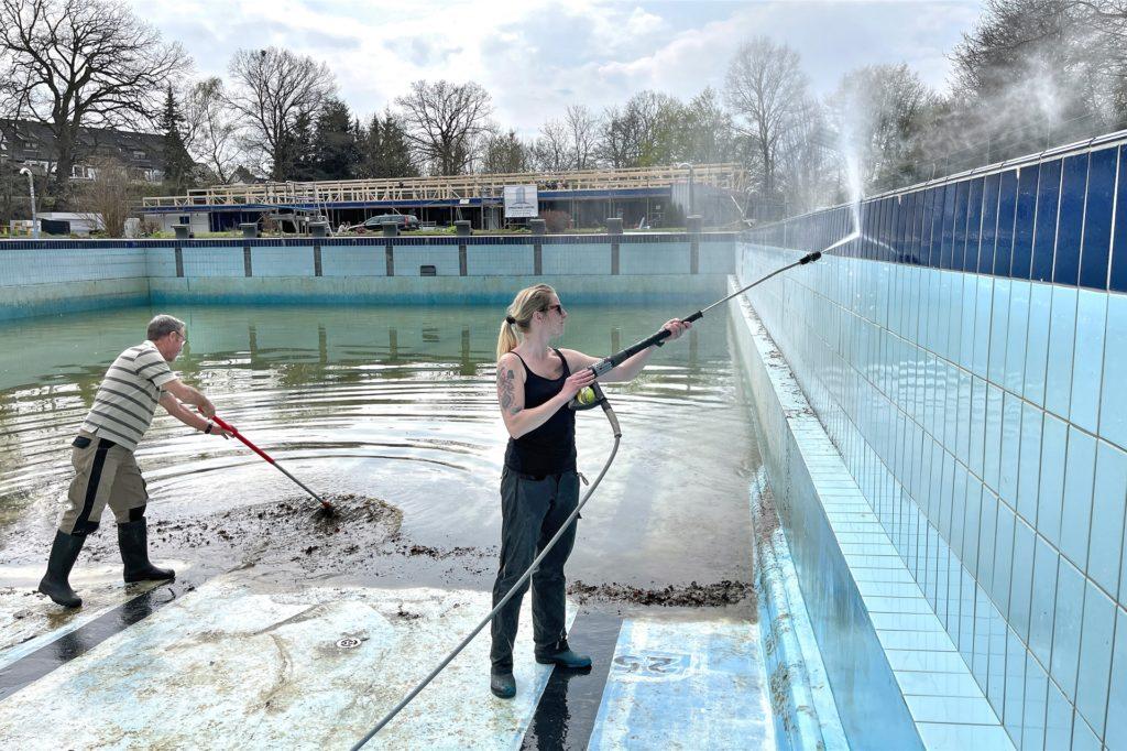 Das Engagement in Dellwig war schon immer groß: Schwimmmeisterin Danielle Werner und Vereinsmitglied Peter Weidemann reinigen das Becken, während die Ehrenamtlichen im Hintergrund fleißig hämmern. Wenn alles gutgeht, könnte der Verein das Becken noch vor der Saison sandstrahlen.
