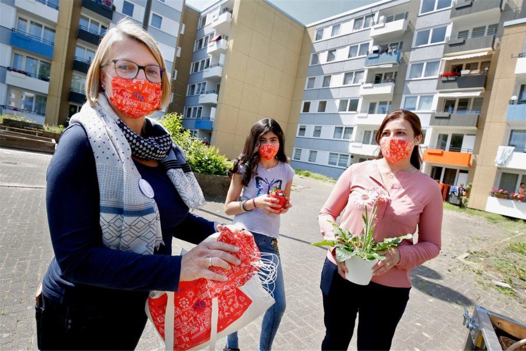 Silke Freudenau übergibt ein Dankeschön an Näherinnen, die ehrenamtlich Mund-Nasen-Schutze für Menschen im Quartier genäht haben.