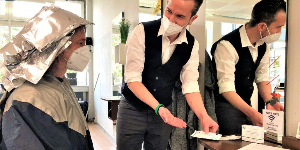 David Ehwein, Inhaber von Coiffeur Thadeusz, ist Dortmunds erster Friseur mit einer eigenen Corona-Schnelltest-Station. Hier zeigt er der Kundin seine Test-Auswahl.