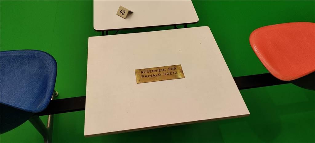 Diese Kombination aus Tischen und Stühlen weist auf Rainald Goetz hin. Er sollte eigentlich ein Buch über die Installation schreiben, tat dies aber nicht. Damit er schreiben kann, ist ein Platz für ihn reserviert.