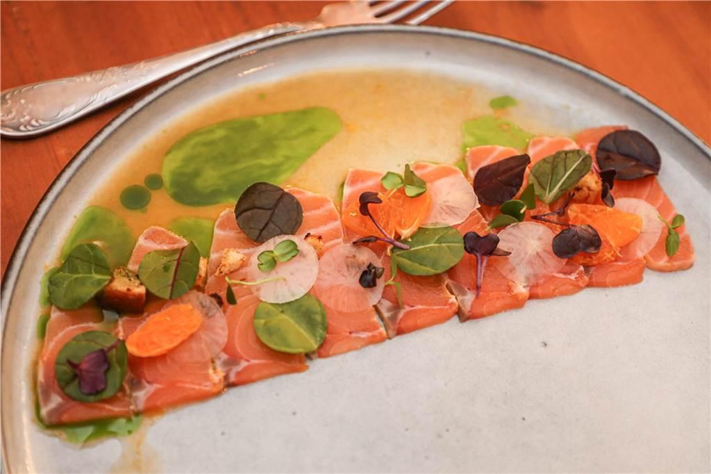 Das Lachs-Carpaccio - leicht gesalzen - in Öl und mit Mandarinen dazu Schnittlauch und Basilikum und kleinen Croûtons.