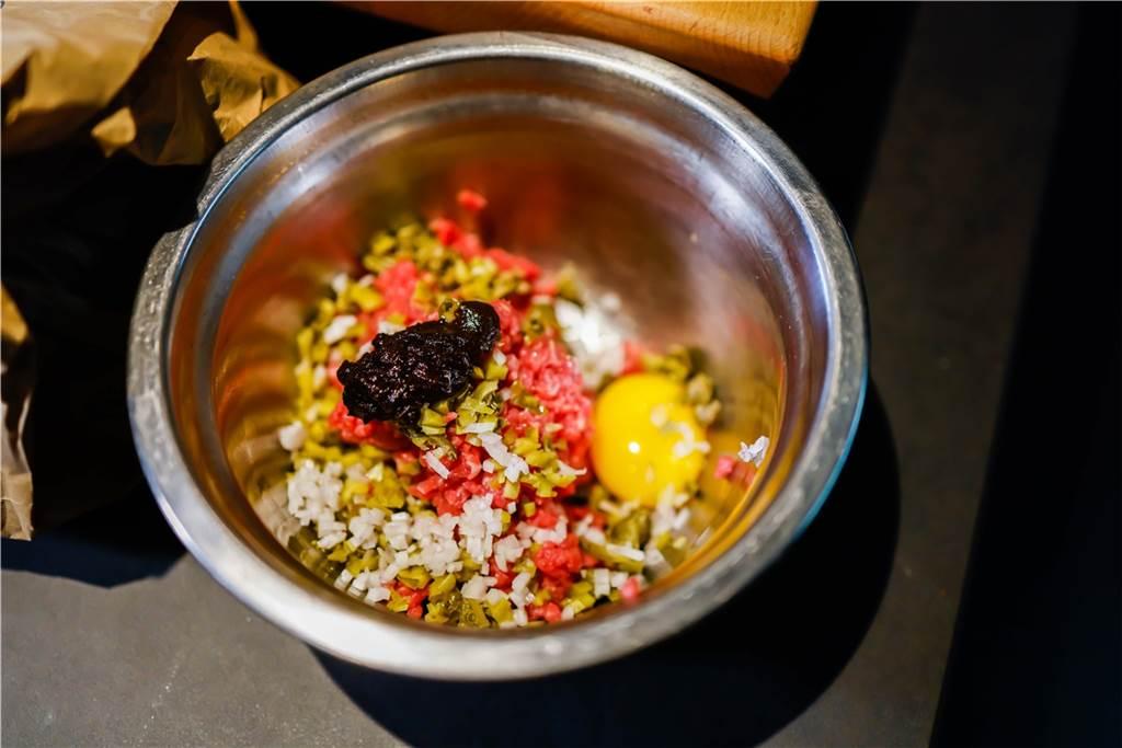 Das Gemisch aus rohem Beef, Schalotten, Cornichons, Kapern, Senf Schwarzem Knoblauch und Zitrone wird zusammen vermengt.