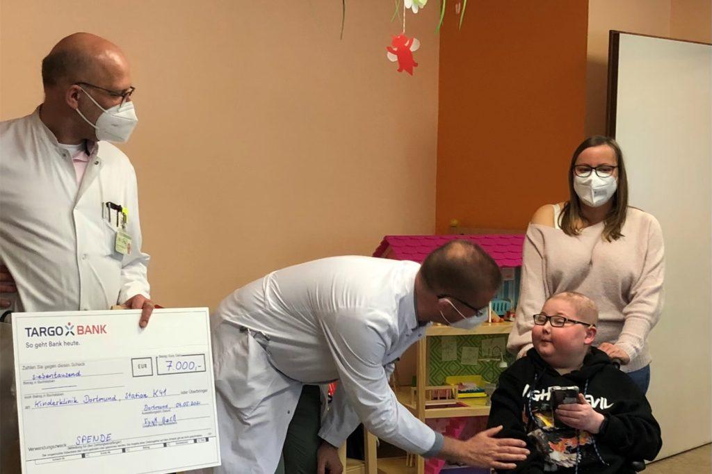 Fynn Born überreicht in der Kinder-Krebsstation des Dortmunder Klinikums einen Spendenscheck: 7000 Euro Erlös aus seinem eigenen Buch.