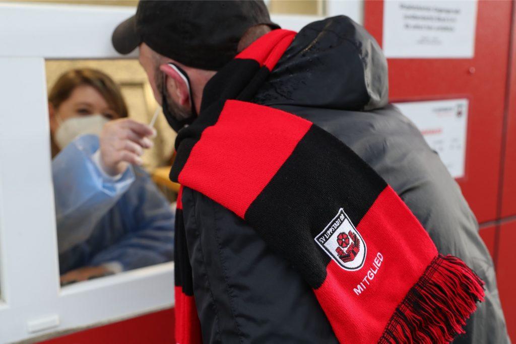 Ein Zuschauer lässt sich vor Spielbeginn beim SV Lippstadt 08 in einem Kassenhäuschen auf das Corona-Virus testen. Die Zugänge waren deshalb  bereits drei Stunden vor Anpfiff geöffnet.