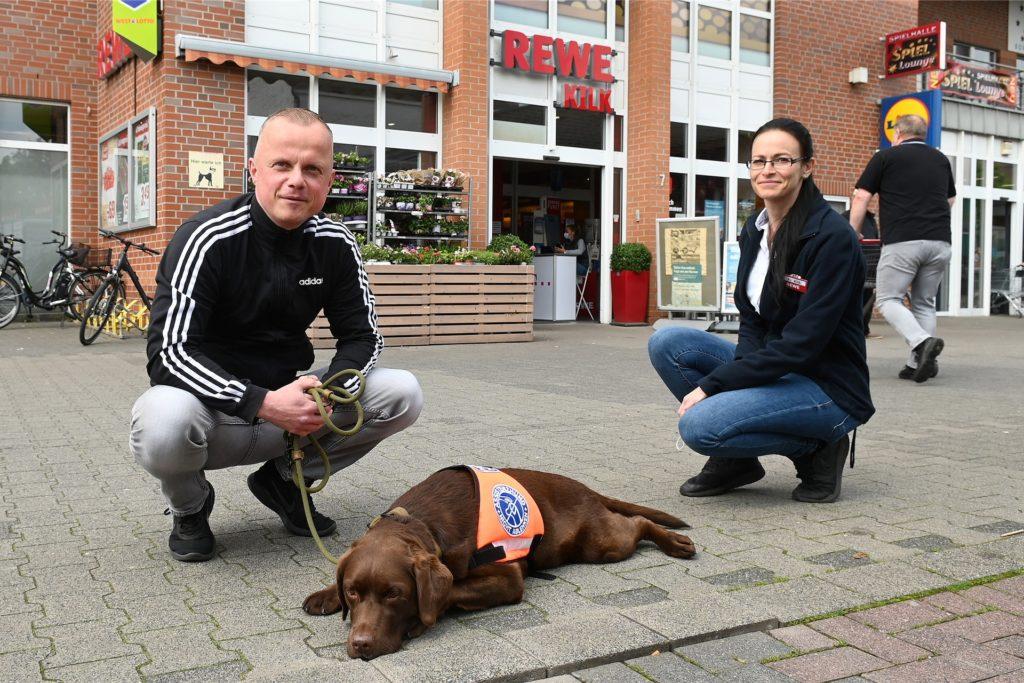 Thorsten Habel mit Assistenzhündin Hanni und der Geschäftsführerin des Rewe Marktes in Wulfen, Anika Kilk.