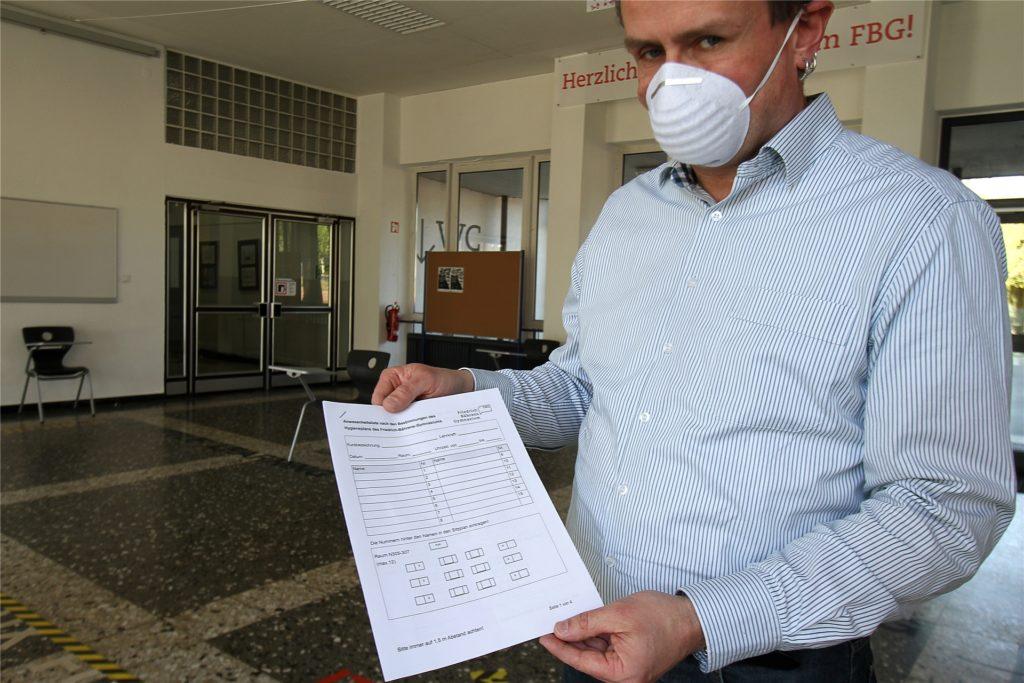 FBG-Schulleiter Heiko Klanke zeigt die Listen, in der die anwesenden Schüler samt Sitzplatz erfasst werden müssen.
