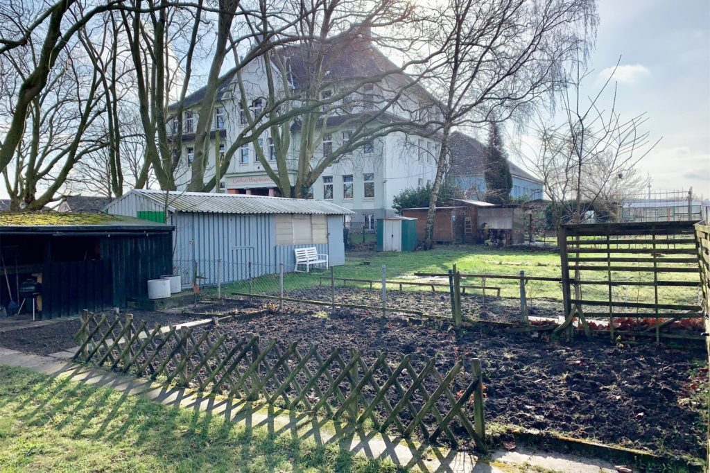 Das aktuelle Schulgebäude: Rechts im Bild sind die Gärten, auf denen das neue Gebäude errichtet werden soll.