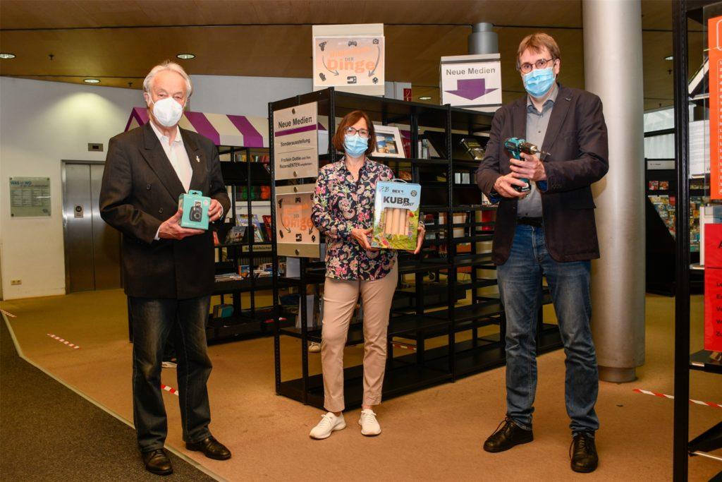 Wolf-Dietrich Koester (Vorsitzender der Freunde der Stadt- und Landesbibliothek), Bibliotheksmitarbeiterin Petra Littmann und Stadt- und Landesbibliotheks-Direktor Dr. Johannes Borbach-Jaene präsentieren ein paar Gegenstände, die ab sofort ausgeliehen werden können.