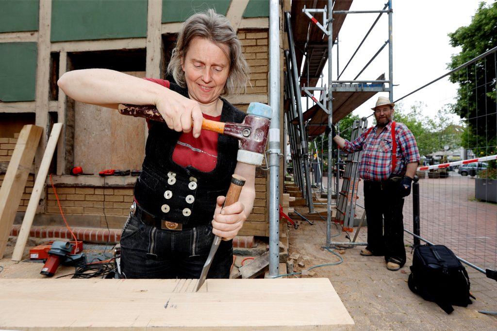 Lehmbau-Expertin und Tischlerin Uta Görler schlitzt einen Balken.