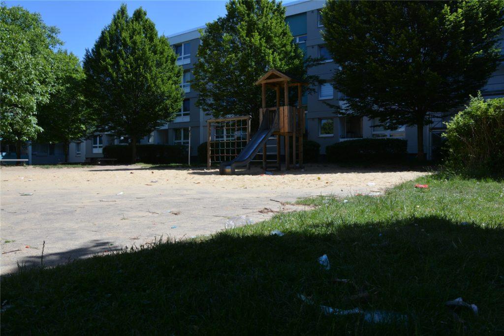Auf dem Spielplatz und den umliegenden Wiesen liegt überall Abfall herum. Die kleinen Punkte im Sand sind weder Blätter noch Holzstöcke, sondern Müll.