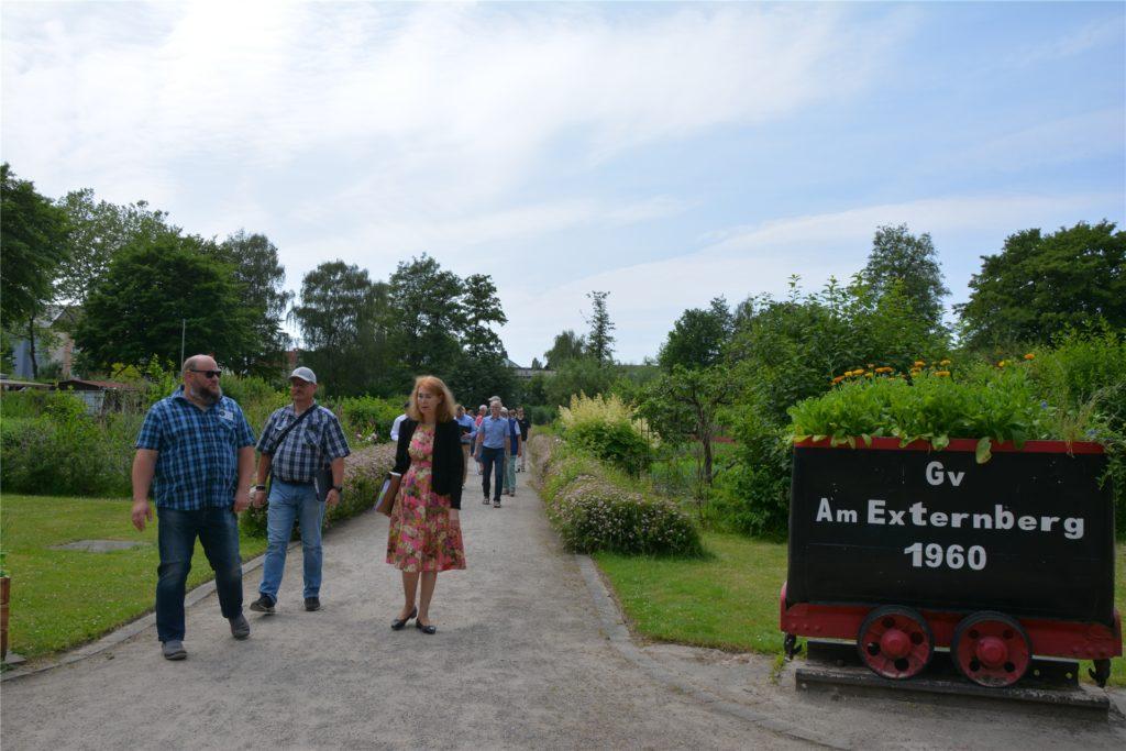 Schriftführer Frederik Kolek (l.) führt die Jury-Vorsitzende Prof. Dr. Dr. Martina Oldengott und den Rest der Gruppe durch die Anlage des Gartenvereins Am Externberg.