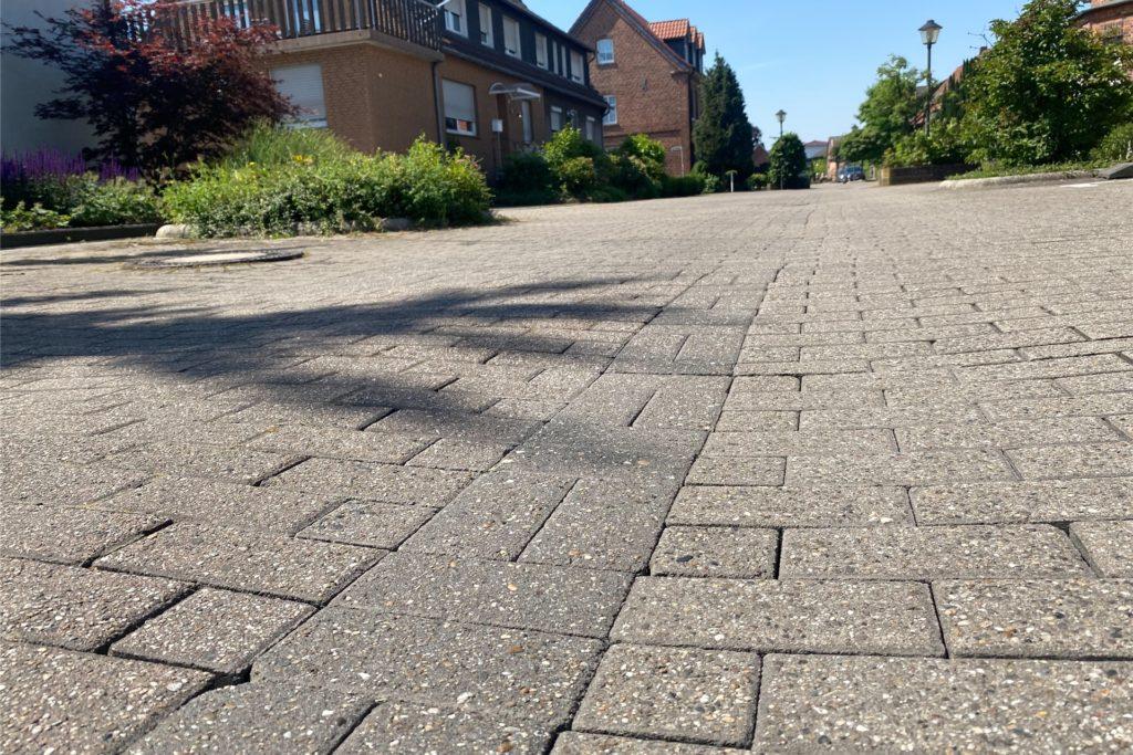 Auf der Dorfheide is die Mitte der Straße teils abgesackt, einzelne Gullis haben sich in kleine Schlaglöcher verwandelt.