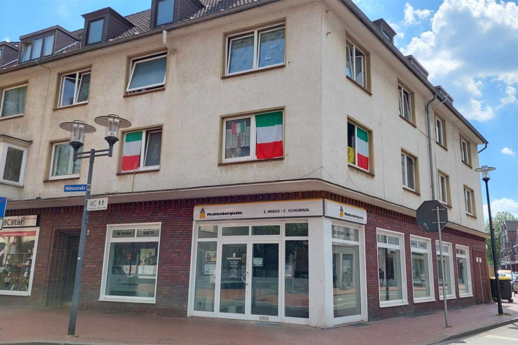 An der Mühlenstraße hängen Fahnen in den Fenstern – italienische.