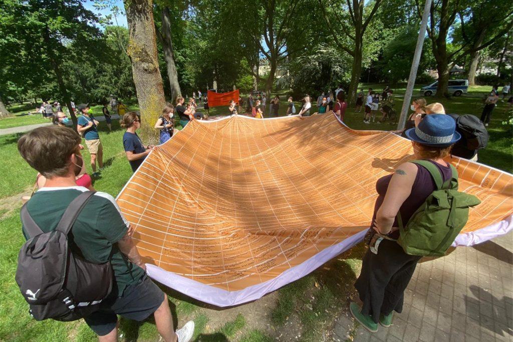 Mit dem Banner, das an Geflüchtete erinnern soll, die im Mittelmeer auf der Flucht ertrunken sind, sind die Teilnehmer im Westpark gestartet.