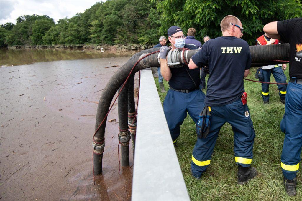 Helfer des Technischen Hilfswerks (THW) lassen Schläuche in die Steinbachtalsperre hinab, um das Wasser abzupumpen.