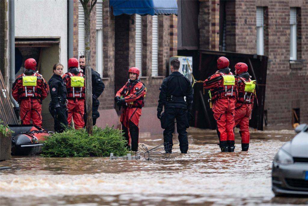 Rettungsschwimmer und Polizeitaucher stehen in einer überfluteten Straße im Ortsteil Blessem.