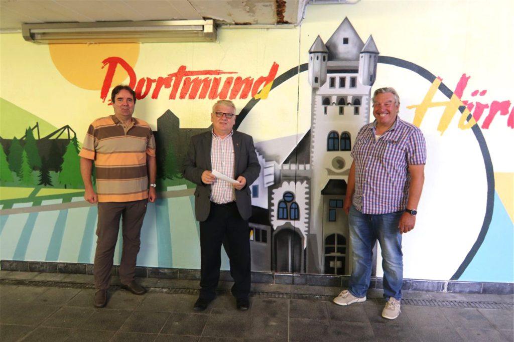 Ralf Neuhaus, Vorsitzender SPD Hörde-Nord, Bürgermeister Norbert Schilff, Werner Baschin, stellvertretender Vorsitzender SPD Hörde-Nord, freuen sich, dass die Wände nun ansprechend gestaltet sind.