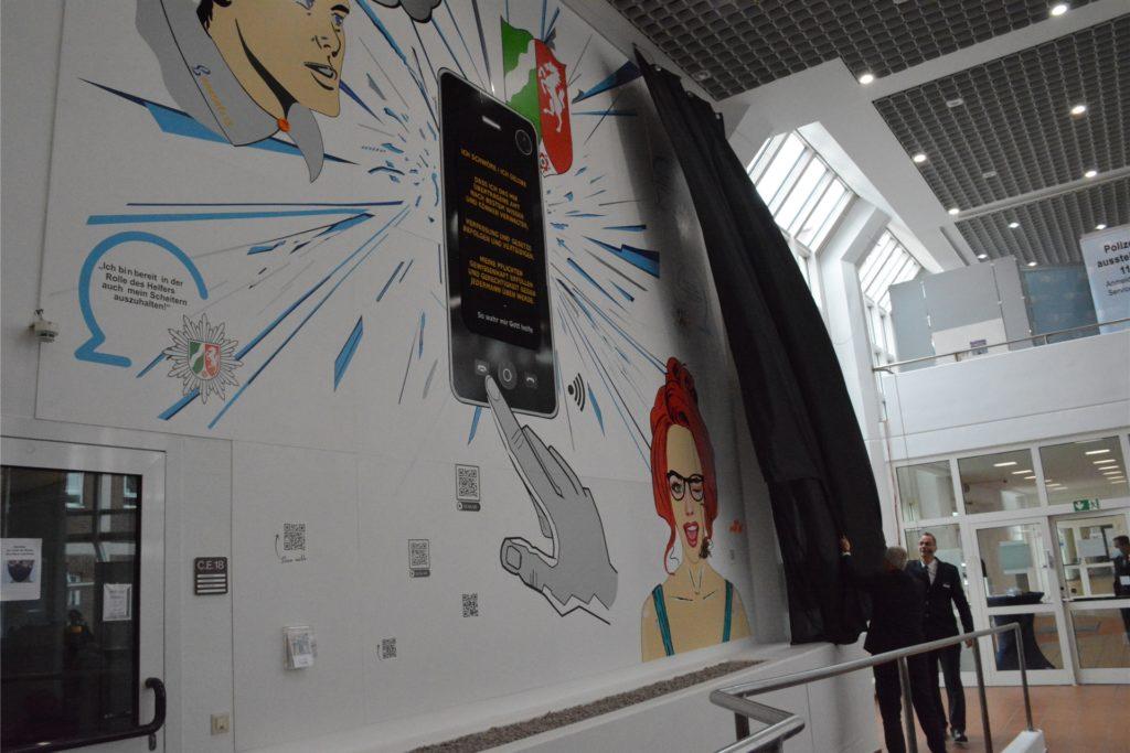 Gregor Lange und Veranstaltungs-Moderator Torsten Sziesze haben ein neues großes Wandbild enthüllt, das die Polizeikräfte an ihren Diensteid erinnern soll.