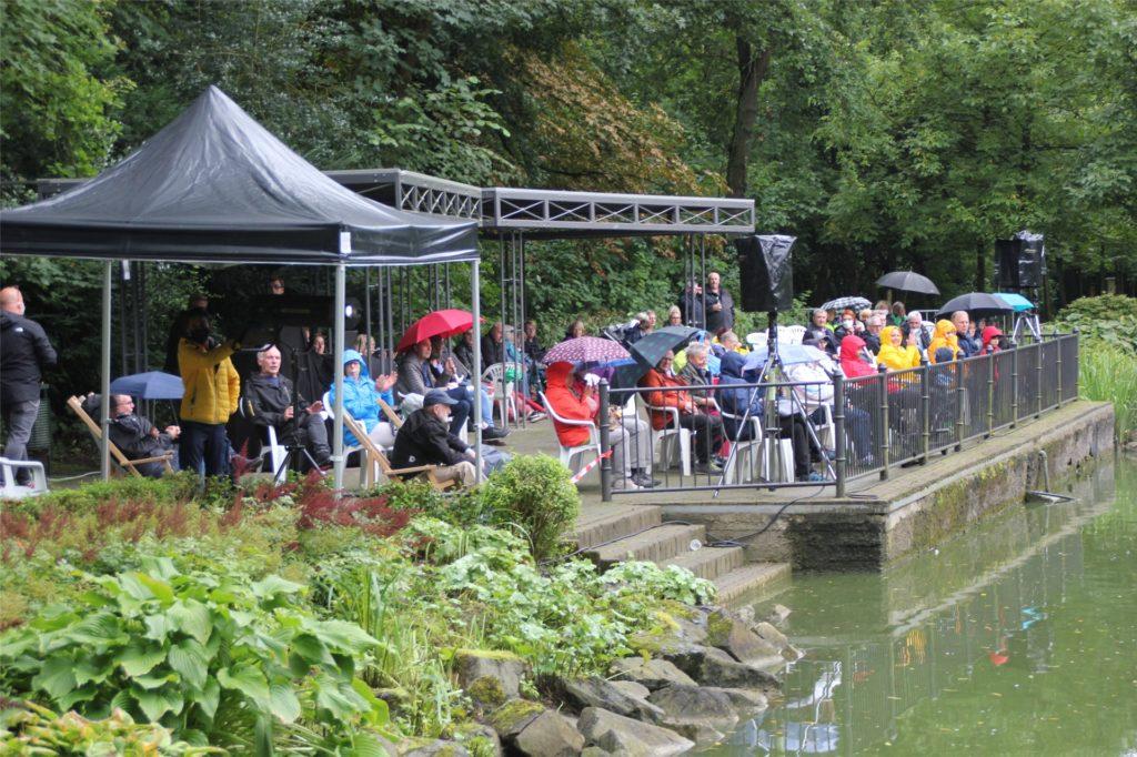 Dem schlechten Wetter zum Trotz waren viele Besucher gekommen. Die Plätze am Ufer boten einen guten Blick auf die Bühne: Die Insel im See des Südparks.