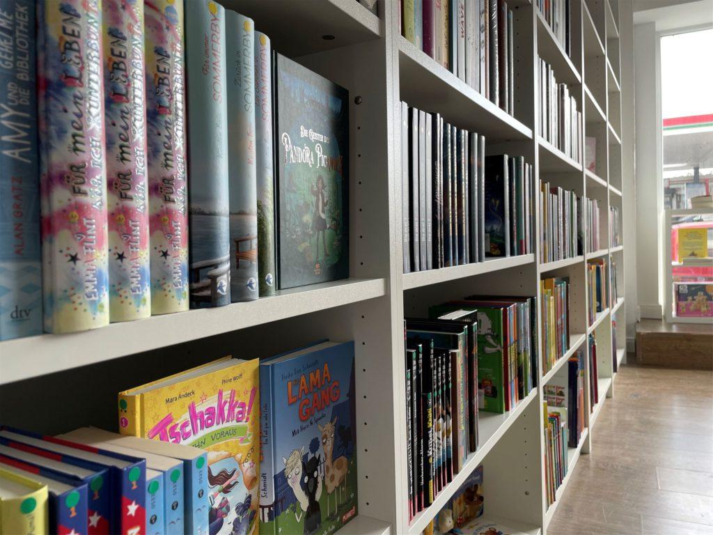 Auf den Buchrücken der Kinderbücher kleben Aufkleber, die anzeigen, für welche Altersklasse das Buch ist. Ganz unten stehen die Bücher für die Kleinsten.