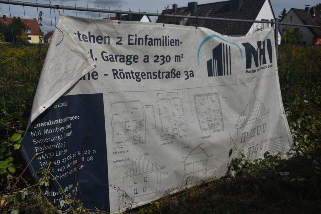 Ein altes Zaunplakat weist noch auf den Bau zweier Einfamilienhäuser hin.